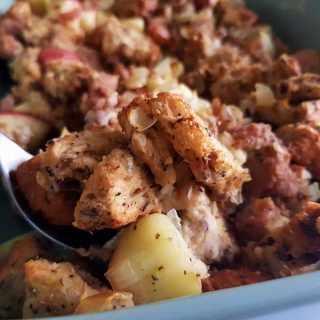 Sausage apple stuffing in a green casserole dish.