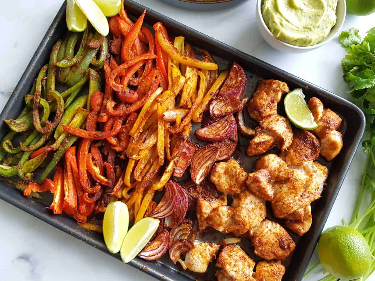 Sheet pan fajitas on a marble table with guacamole, cilantro and lime wedges on the side.