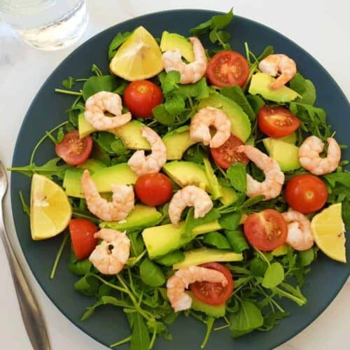 Shrimp and avocado salad on a blue plate on a marble table with a fork and a glass of water next to it.
