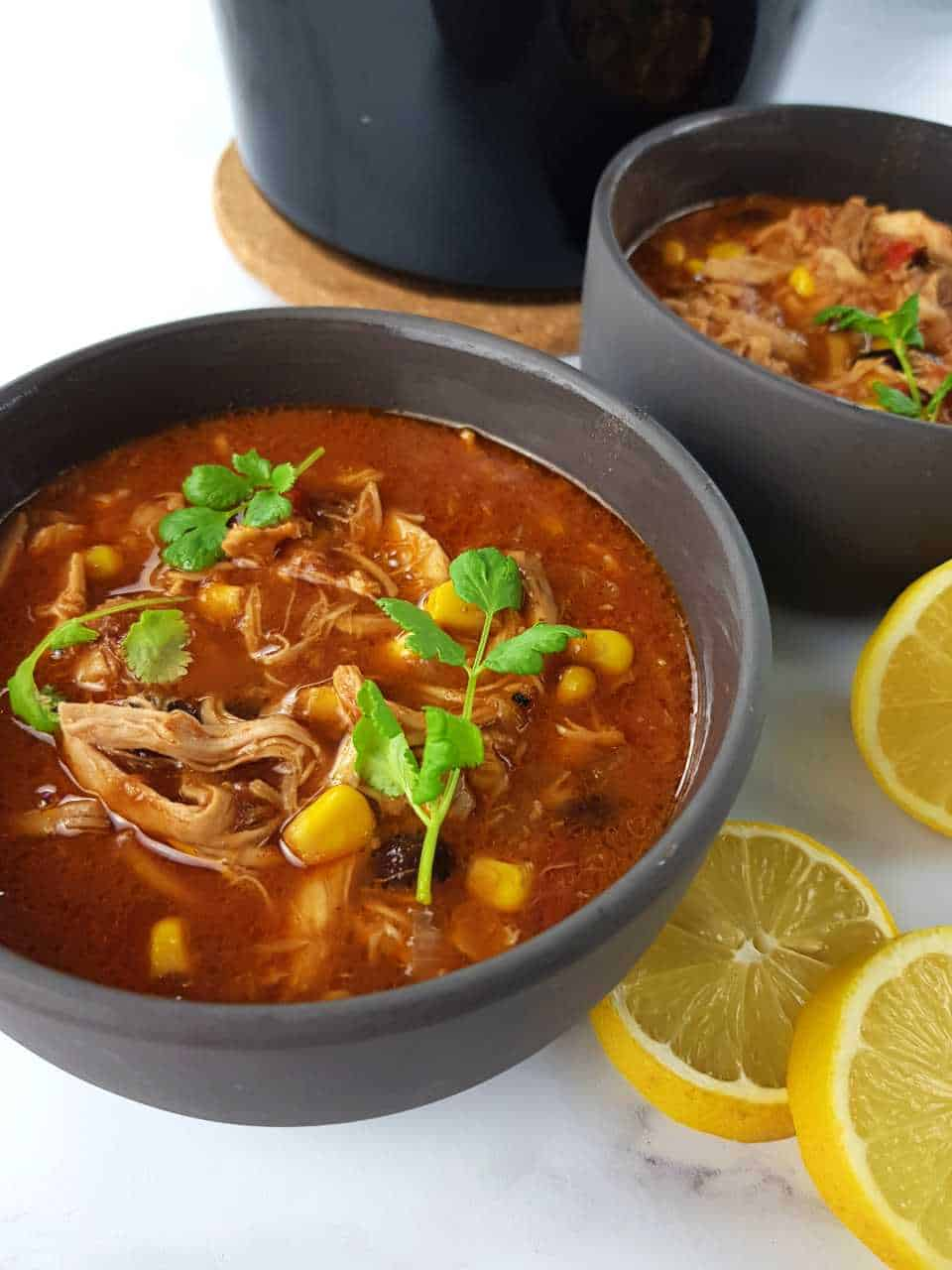 Slow cooker chicken taco soup in gray bowls.