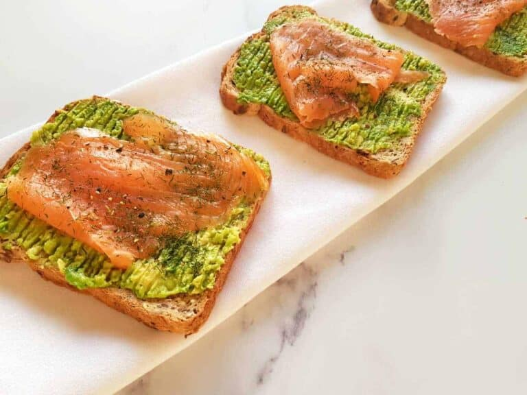 Smoked salmon and avocado toast on a marble table.