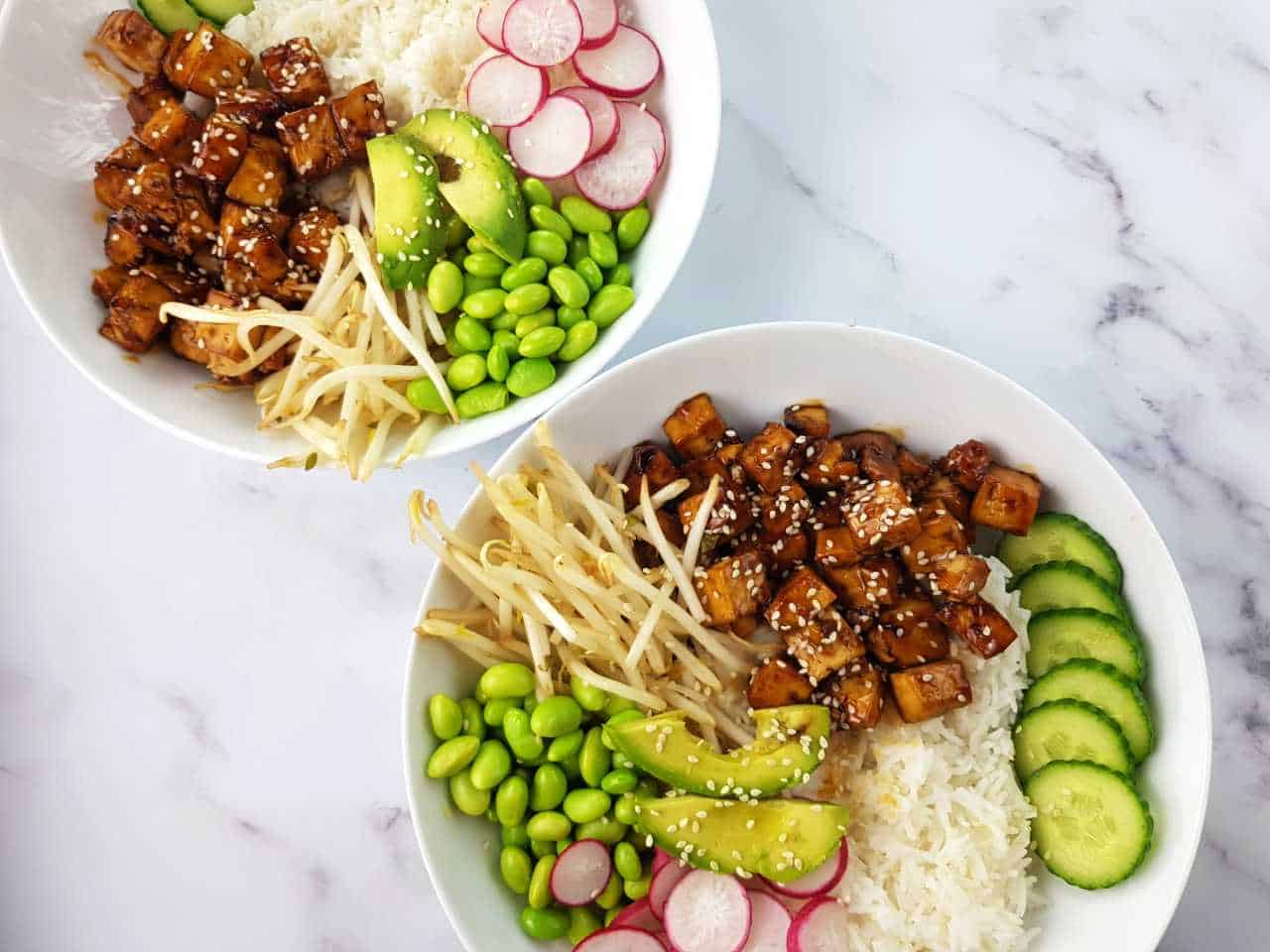 Teriyaki tofu in white bowls on a marble table.