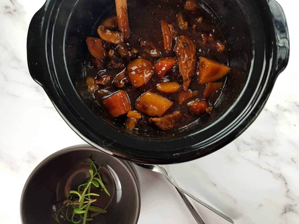 Beef and ale stew in the slow cooker on a marble table, with gray bowls and forks in front.