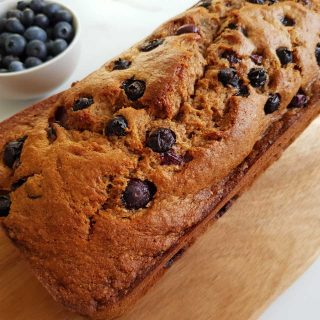 Banana & blueberry bread on a wooden board on a marble table with a bowl of blueberries on the side.