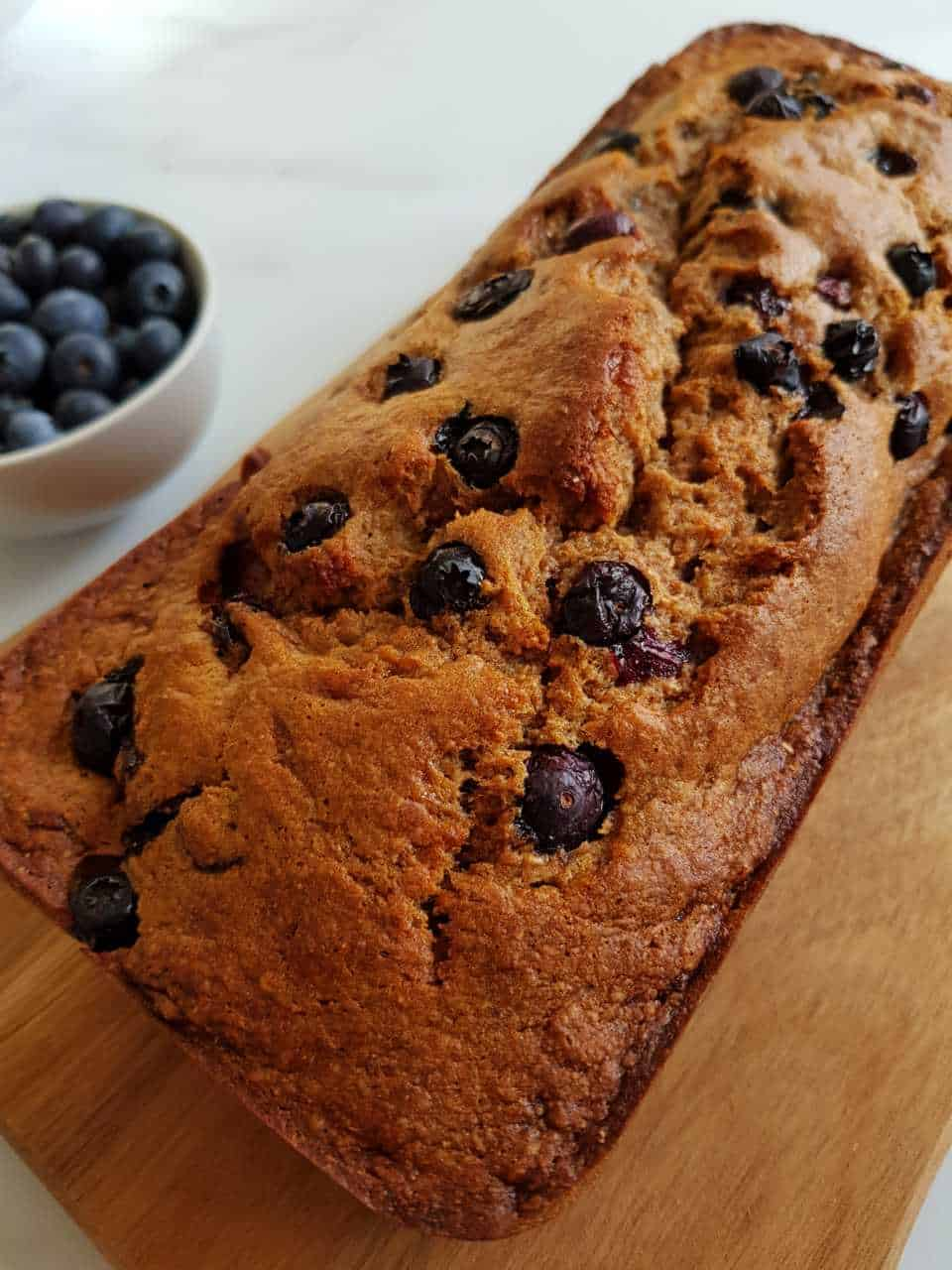 Banana bread with blueberries on a wooden board with a bowl of blueberries on the side.