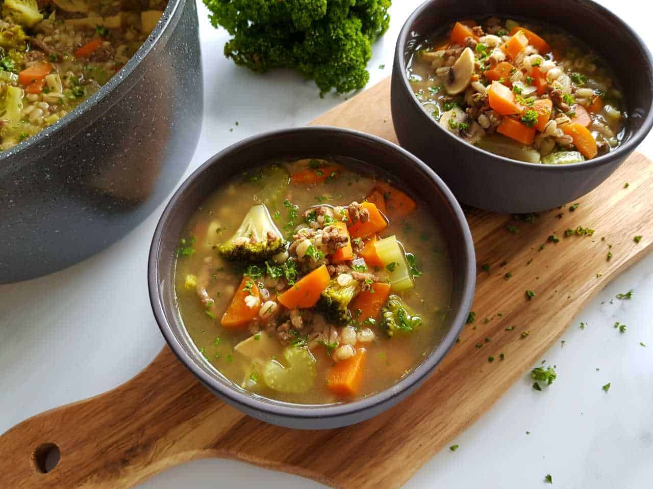 Barley soup with ground beef in bowls on a wooden chopping board.