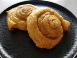 Cinnamon puff pastry rolls on a black plate.
