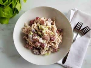 Grape and chicken salad in a white bowl on a marble table. Forks places on a white napkin on the side.