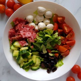 Italian salad in a white bowl on a marble table with cherry tomatoes scattered around.