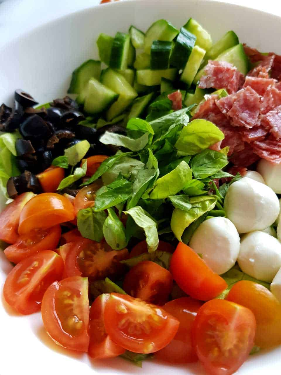 Italian salad with salami in a white bowl.