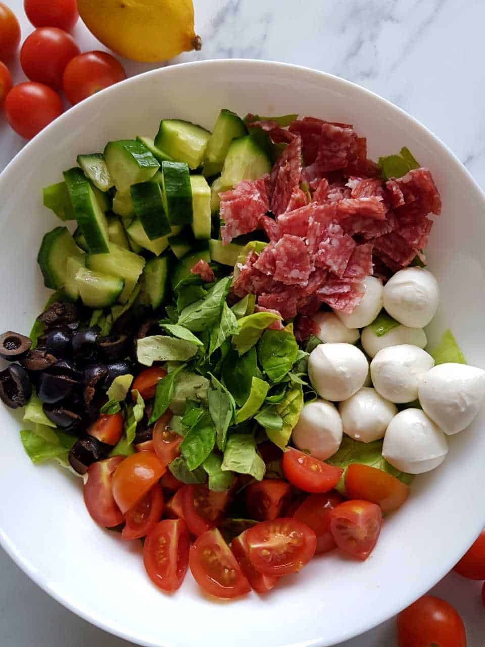 Italian salad in a white salad bowl on a marble table.
