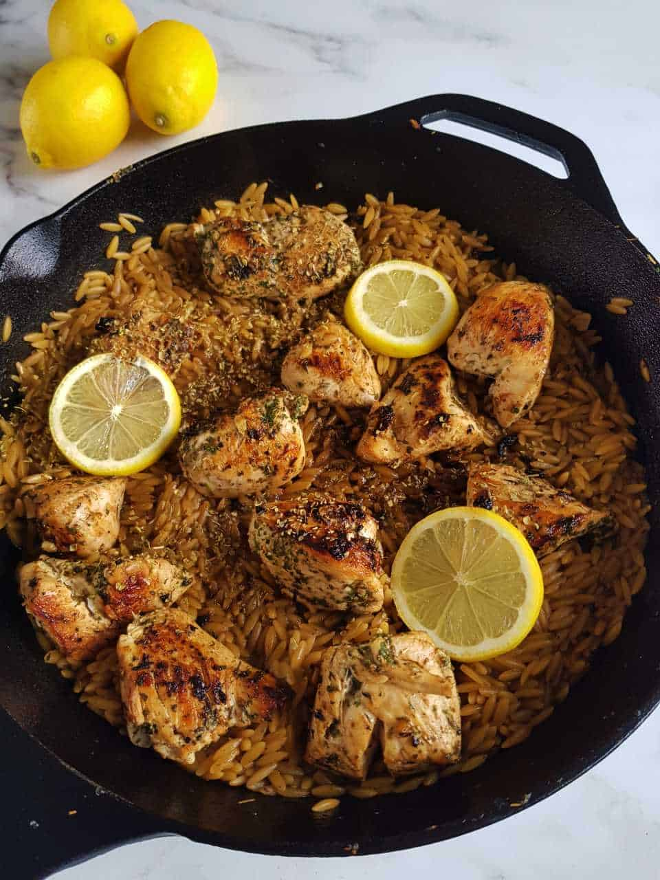 Lemon chicken with orzo in a cast iron pan.