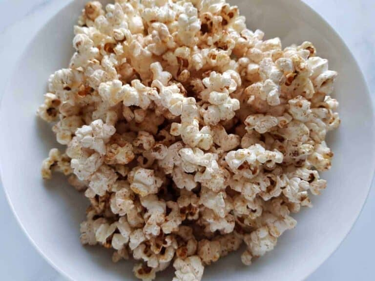 Popcorn with honey and cinnamon in a white bowl.