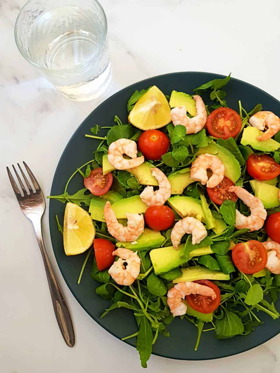 Prawn and avocado salad on a blue plate on a marble table.