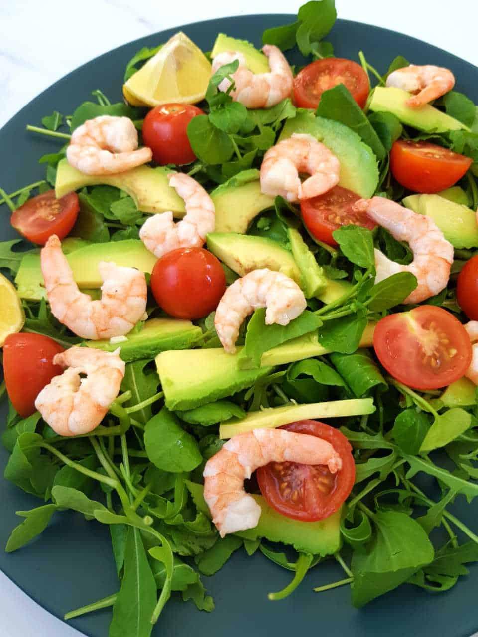 Shrimp avocado salad on a blue plate.