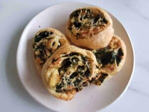 Spinach and feta pinwheels on a white plate on a marble table.