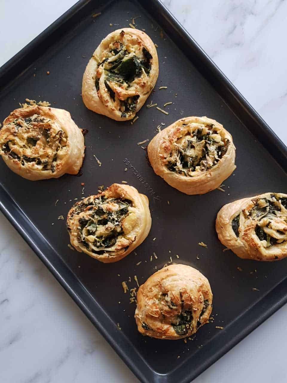 Spinach and feta puff pastry pinwheels on a baking tray on a marble table.
