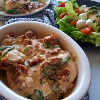 Tuscan chicken in a white bowl on a gray tea towel. A mixed side salad in the background.