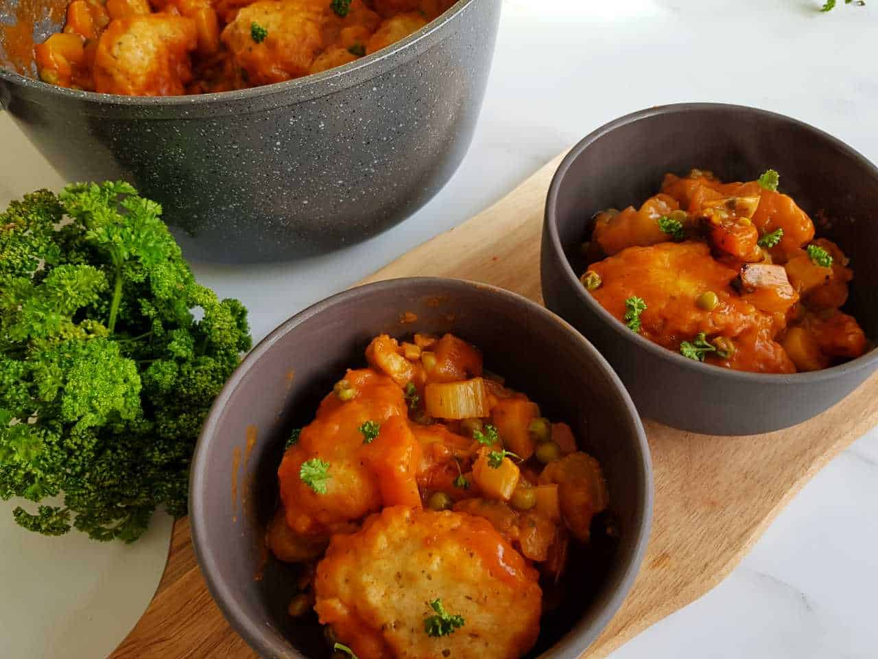 Vegetable stew with dumplings in gray bowls on a wooden chopping board.