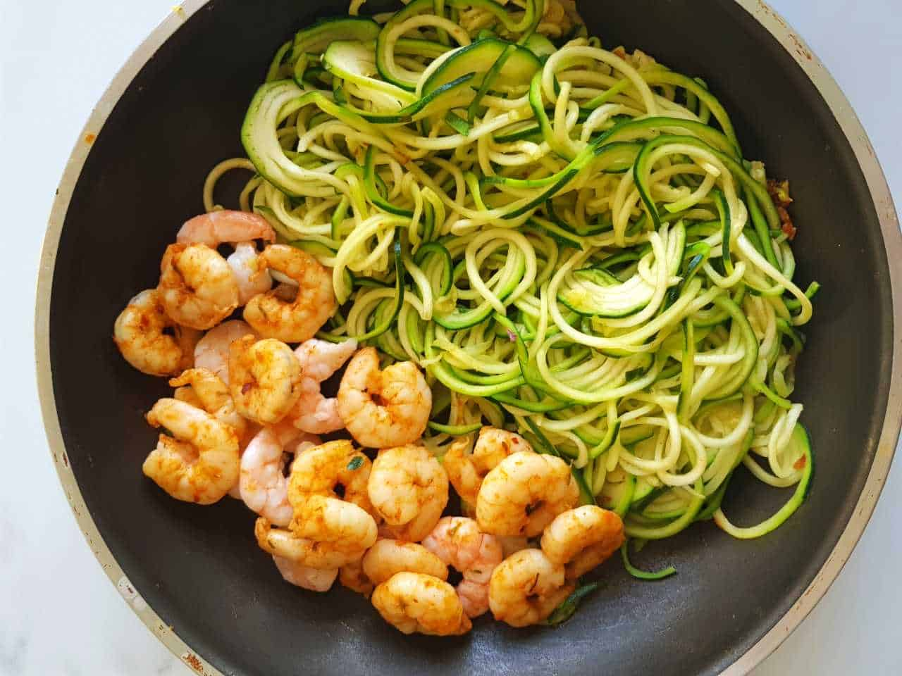 Zucchini noodles and shrimp in a pan on a marble table.