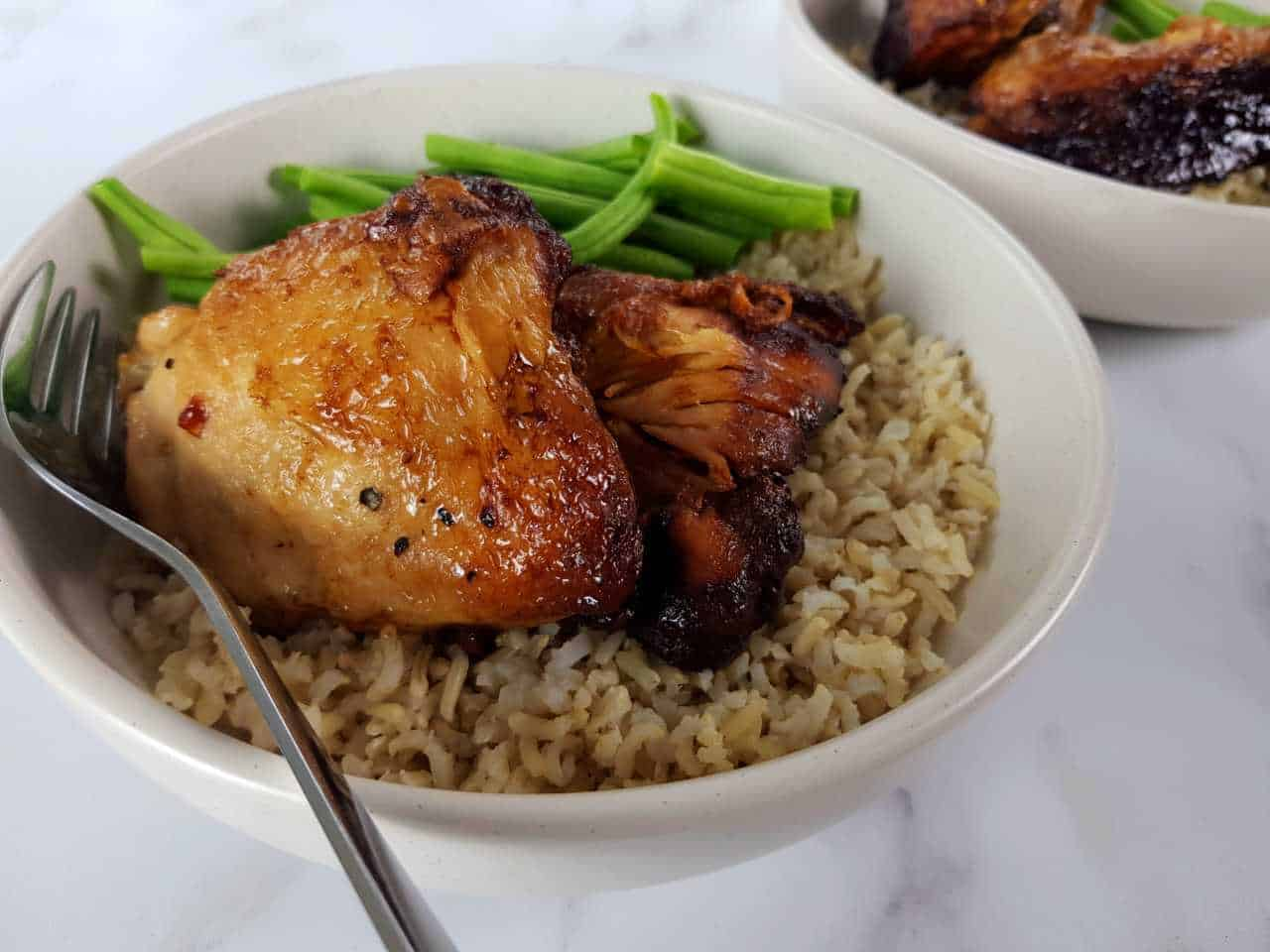 Adobo chicken in a white bowl with rice and green beans on a marble table.