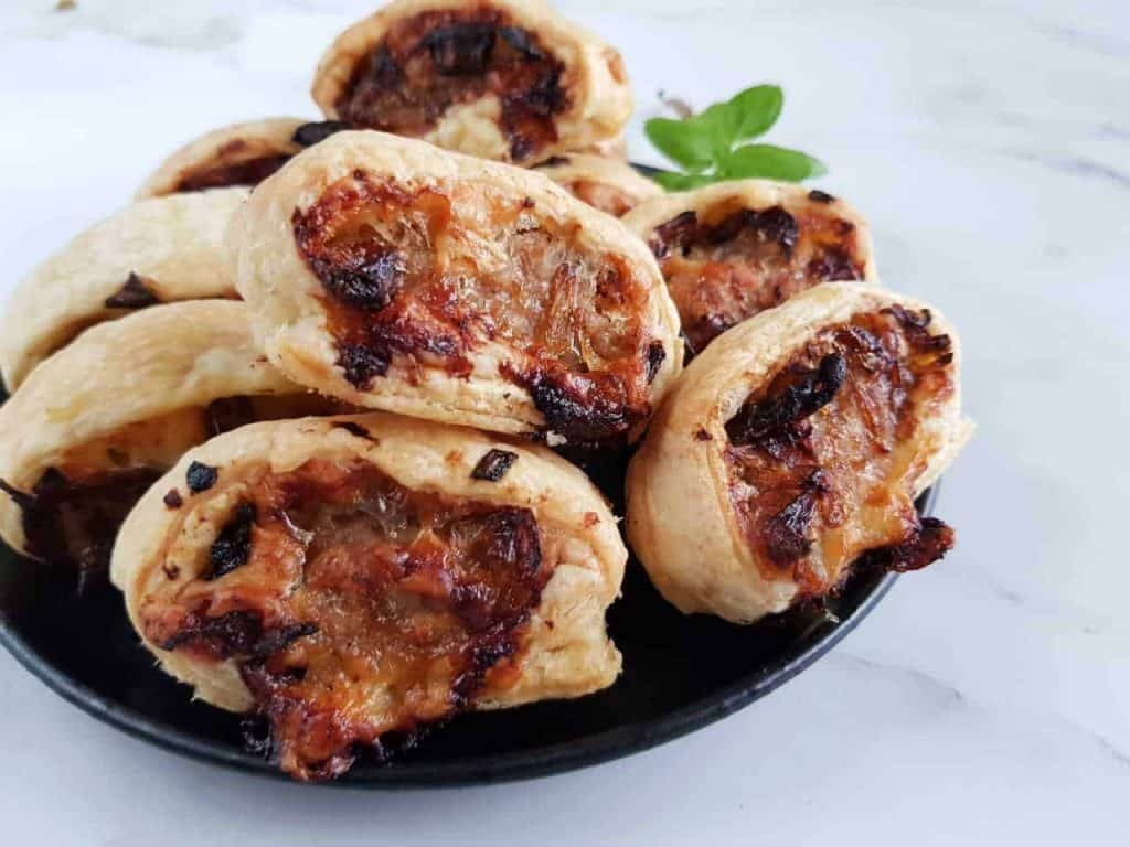 Caramelized onion and cheese sausage rolls on a black plate.