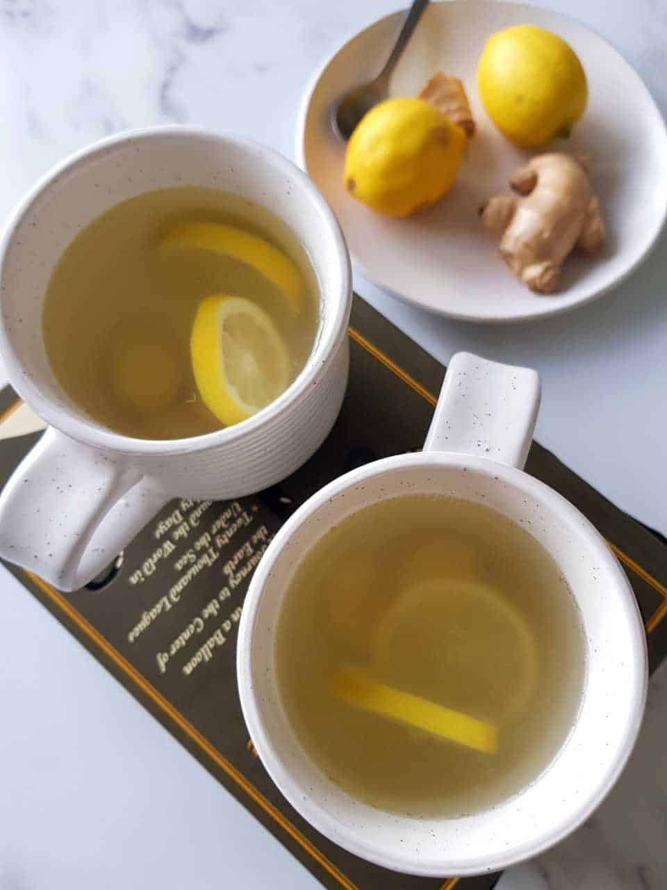 Hot lemon and ginger drink in cups on top of a book on a marble table.