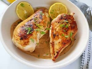 Lemon pepper chicken on a white plate with cutlery and lemon slices on the side.