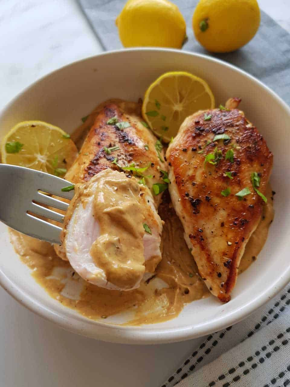 Lemon pepper chicken breasts in a white bowl with lemons in the background.