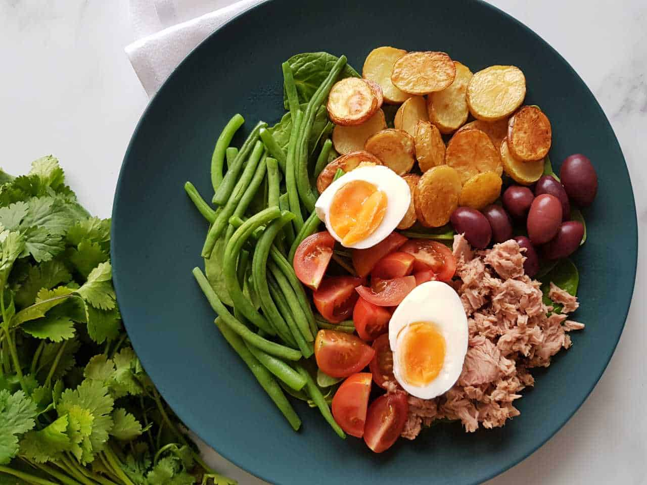 Nicoise salad on a blue plate on a marble table with fresh herbs on the side.