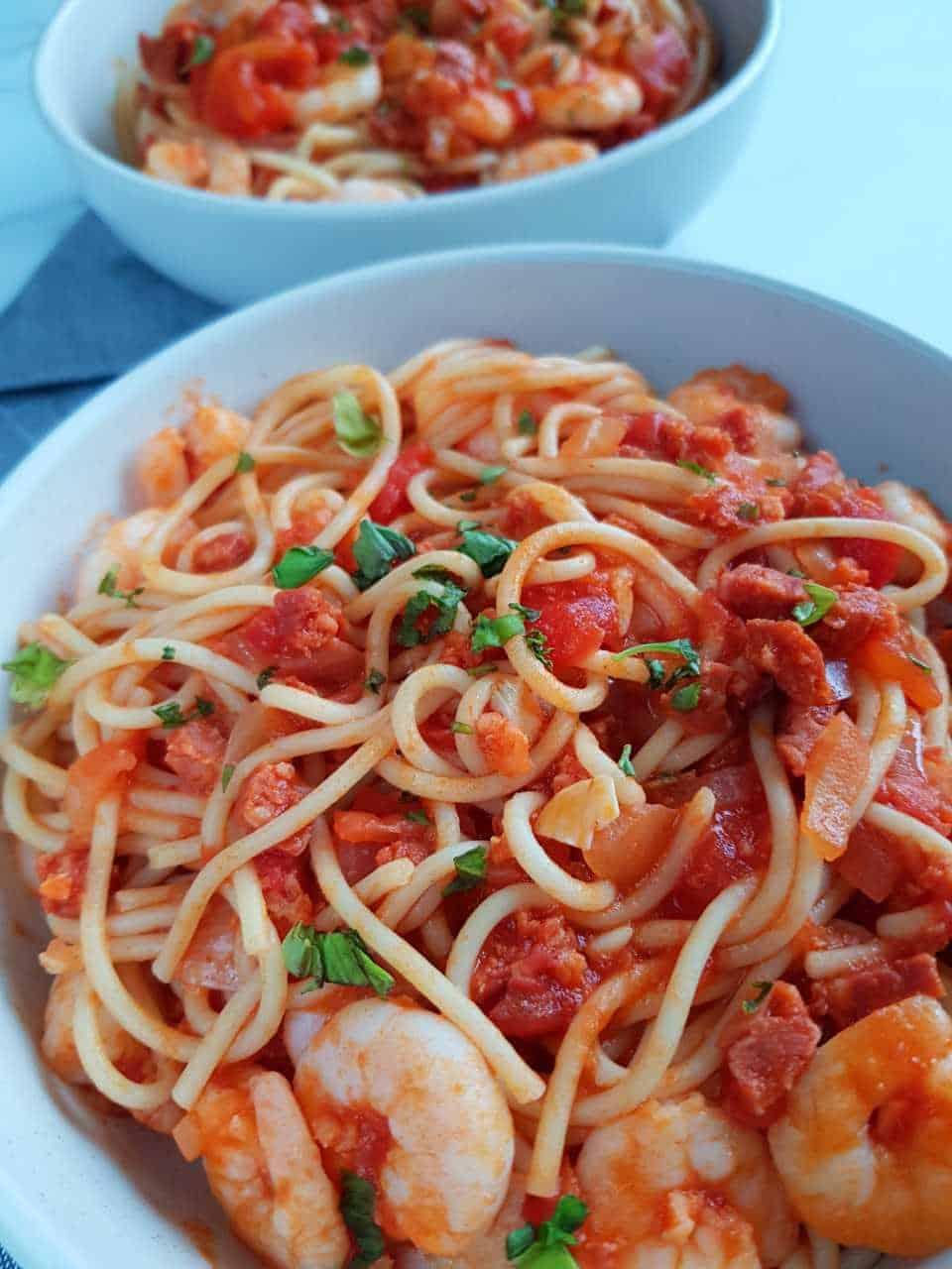 Pasta with prawns and chorizo in white bowls.