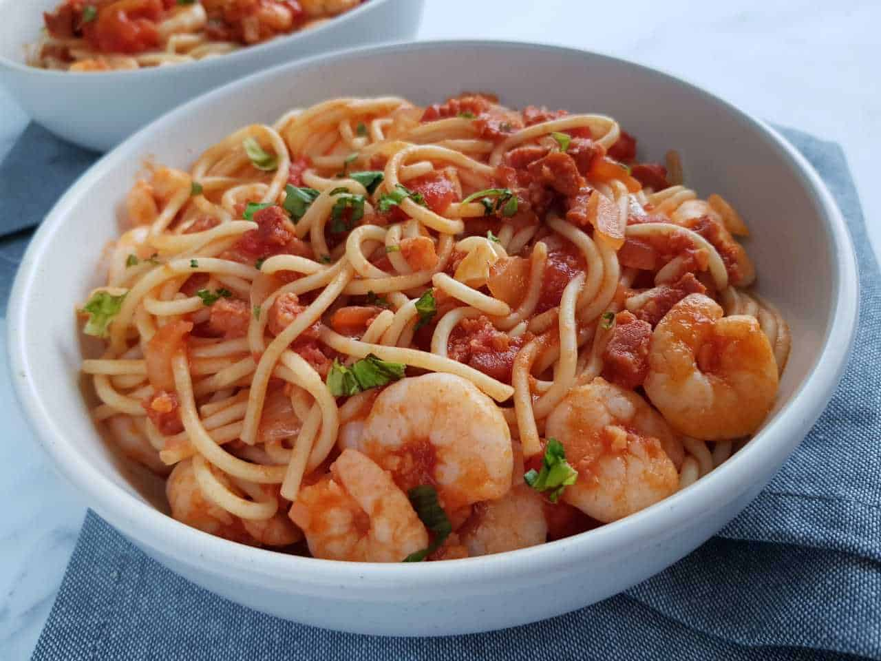 Prawn and chorizo pasta in a white bowl on a gray table cloth.