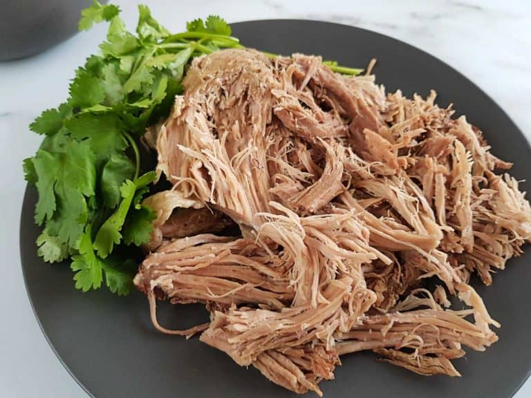 Pulled pork on a gray plate on a marble table.