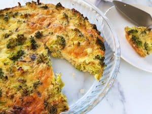 Quiche without crust in a quiche tin. A slice served on a white plate next to it.