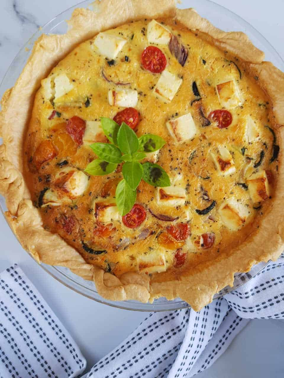 Roasted vegetable and feta quiche on a marble table with a tablecloth on the side.