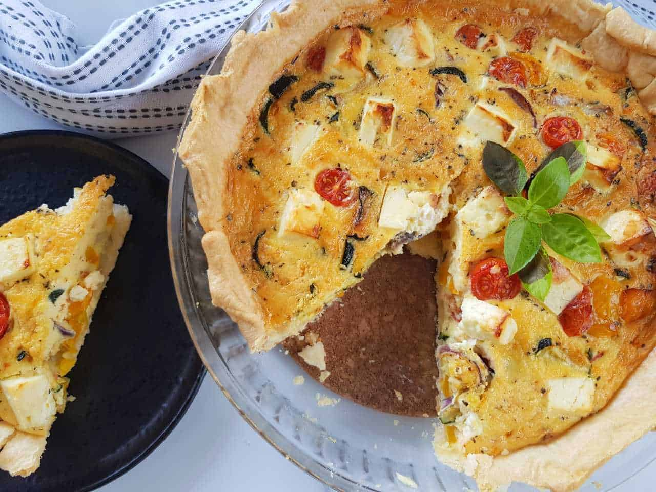 Roasted vegetable quiche with feta on a table, with a slice plated on the side.