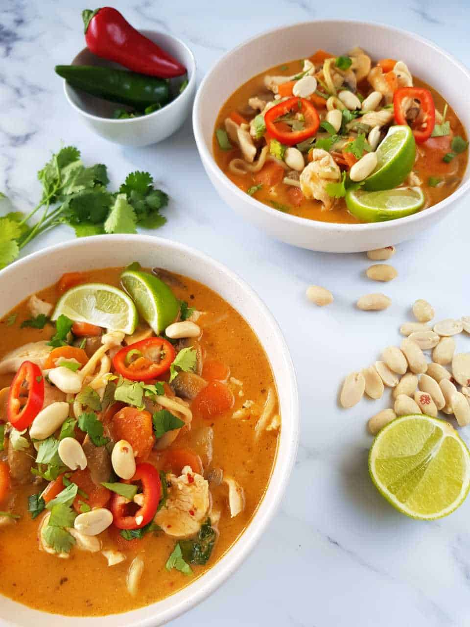 Thai chicken noodle soup in white bowls on a marble table with peanuts, lime, fresh coriander and chili scattered.