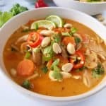 Thai chicken ramen in a white bowl with garnish scattered.