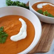 Thai curried sweet potato soup in white bowls on a wooden board.