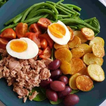 a plate of nicoise salad with eggs, tuna,potatoes and green beans.