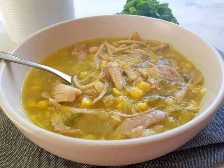 chicken & sweetcorn soup in a white bowl with herbs in the background.
