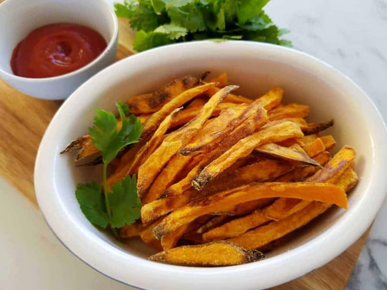 oven baked sweet potato chips on a wooden board with ketchup.