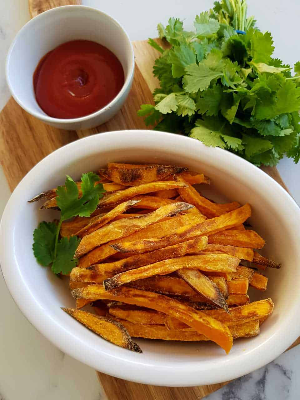 sweet potato fries on a wooden board with tomato sauce and fresh herbs.