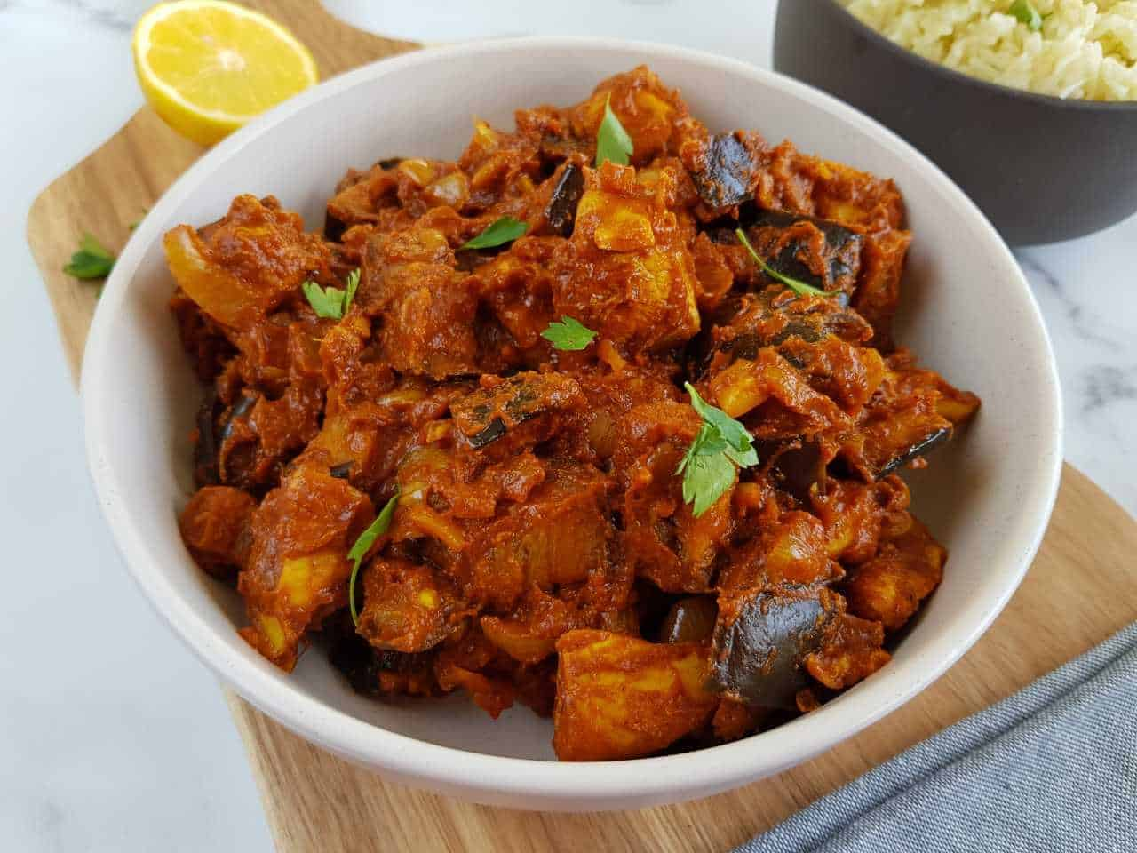 Chicken and aubergine curry in a white bowl.