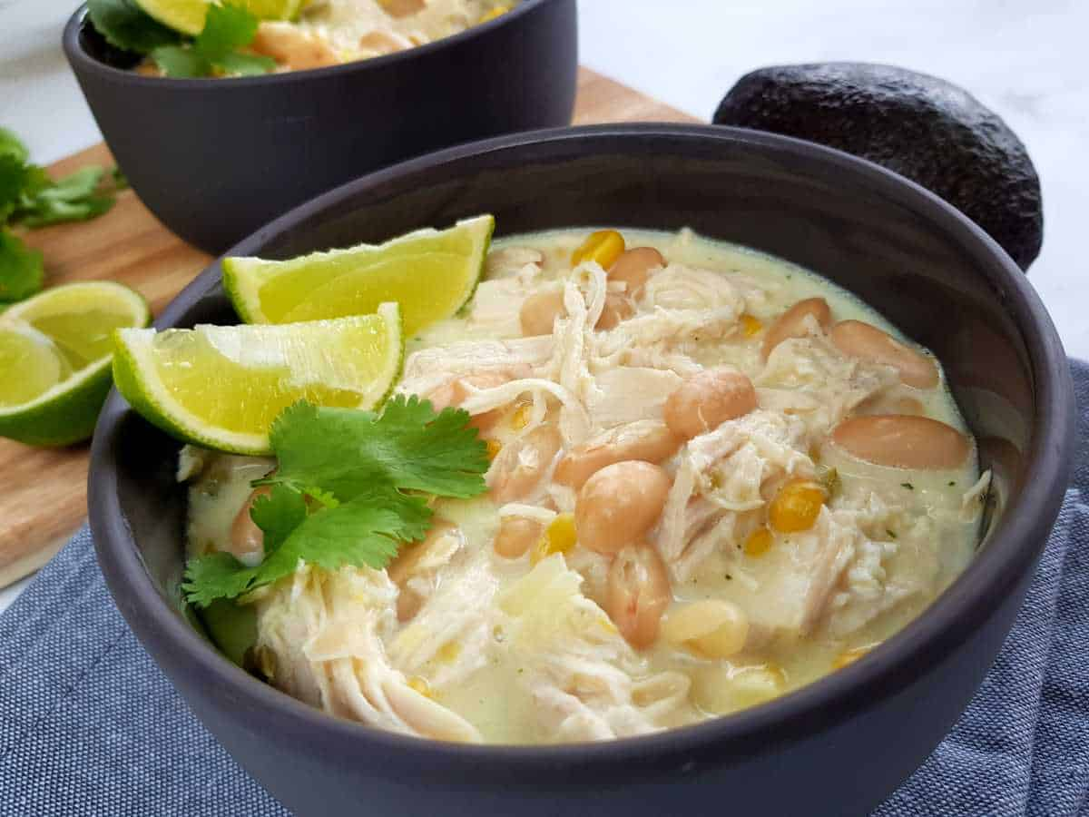 White chicken chili in gray bowls with lime and herbs on top.