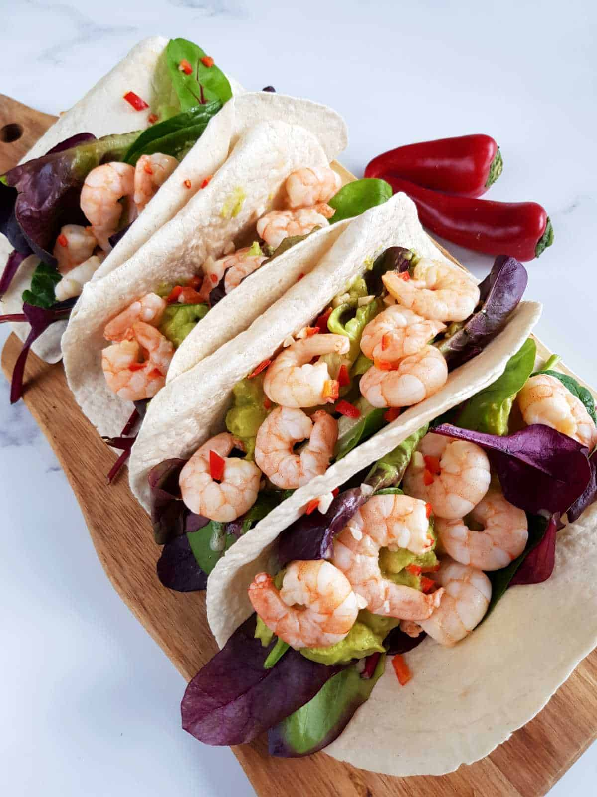 Chili and lime shrimp tacos on a wooden board.