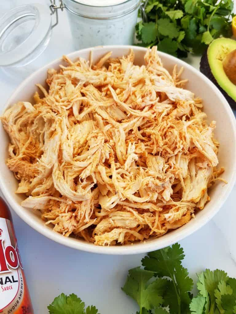 Shredded buffalo chicken in a bowl with buffalo sauce, ranch, avocado and cilantro on the side.