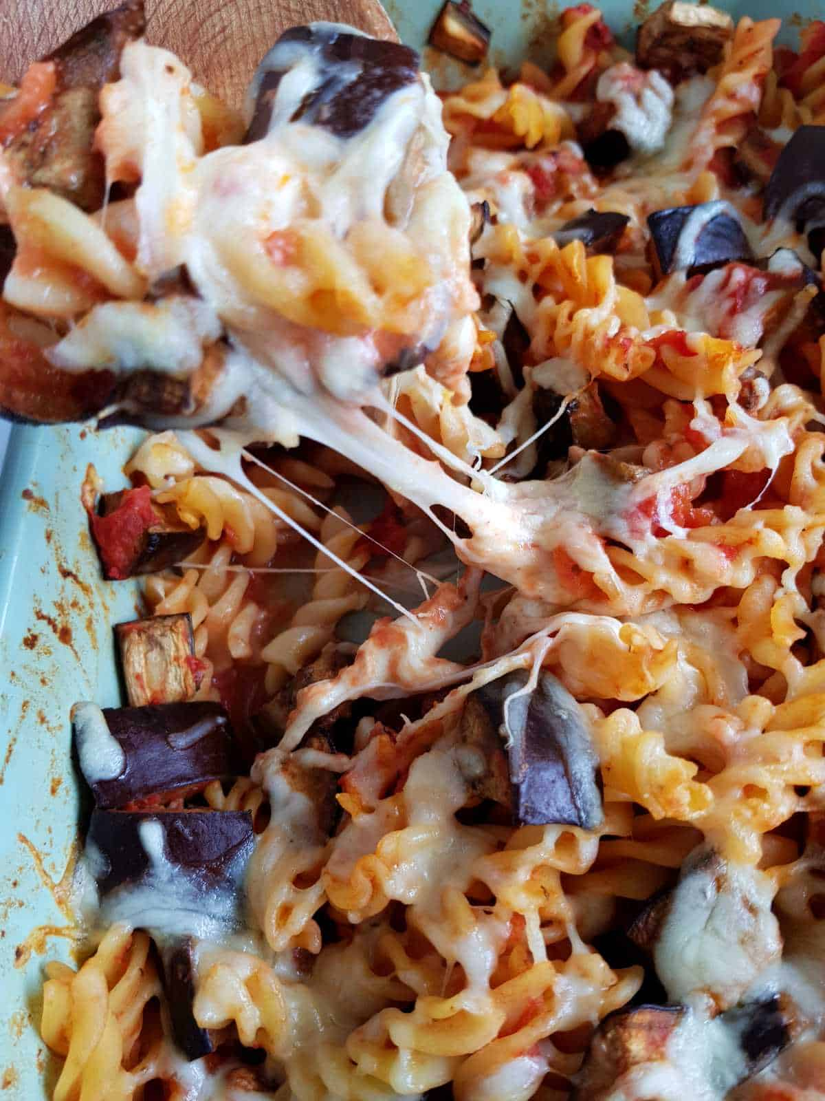 A wooden spoon is lifting out a serving of eggplant mozzarella pasta bake, creating strings of cheese.