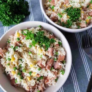 a bowl of fried rice with gammon, peas and corn.