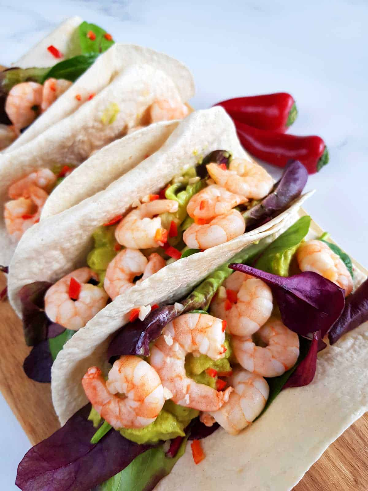 Lime and chili shrimp tacos with fresh chilies on the side.